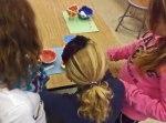 Girls examine glazed ceramic WOW pieces.