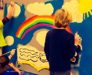 Fourth graders paint a large mural for the library