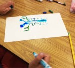 A student paints water on top of marker drawing to soften the color.