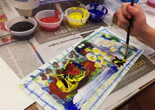 This student is painting with tempera paint on top of chalk and oil pastel, marker painting and watercolor.