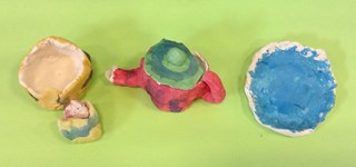 Younger students decorate their art with watercolor.