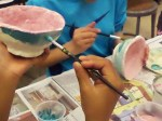 Painting glaze designs on fired clay.