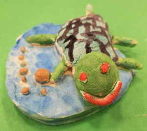 A first grader makes a frog in the water.